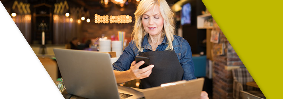 A Lead Bank business community client using the Lead Bank online mobile app on her phone and computer
