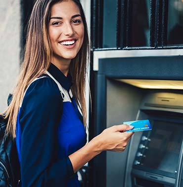 A woman using an ATM with an instant-issue ATM debit card from Lead Bank